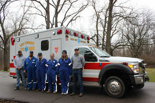 Six members of the Reily Township EMS squad stand in front of a Reily Township ambulance.