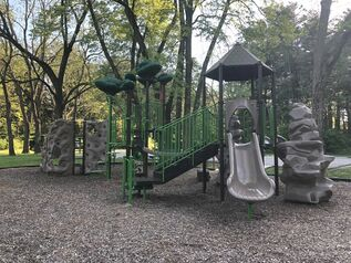 The Springfield Road Area. The playground is in a mulched area, and is complete with a climbing wall and a slide. Benches sit around the playground, and the area is surrounded with green grass and trees.